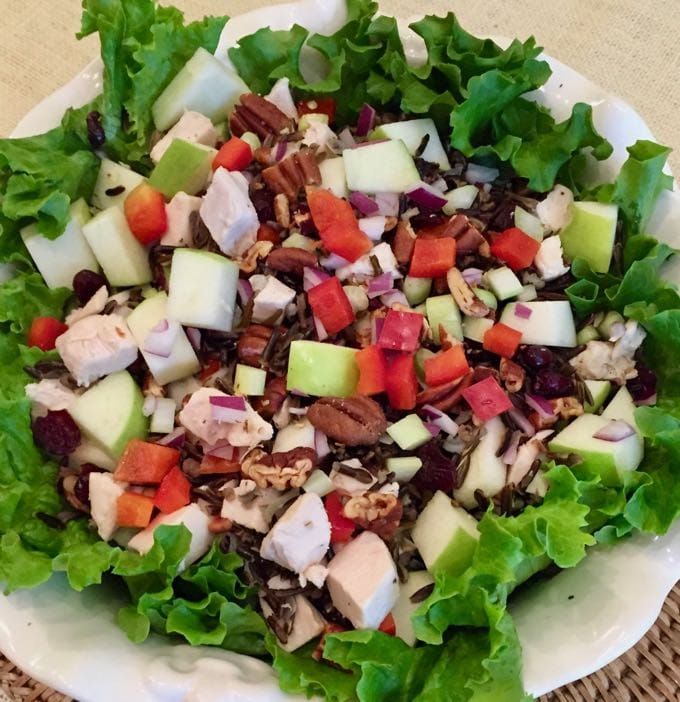 Healthy Wild Rice Chicken Salad on lettuce leaves in a large white serving bowl