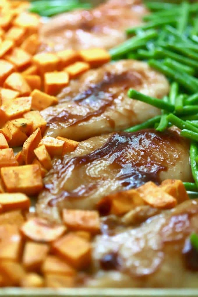 A sheet pan with sweet potato cubes, chicken breasts covered with BBQ sauce and green beans.