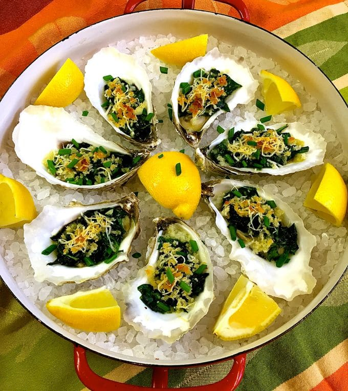 Oysters Rockefeller in oyster shells on a bed of salt with lemon garnish.