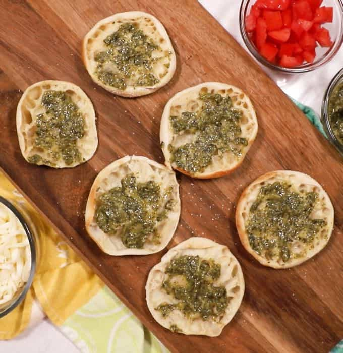 English muffin halves topped with pesto on a cutting board.