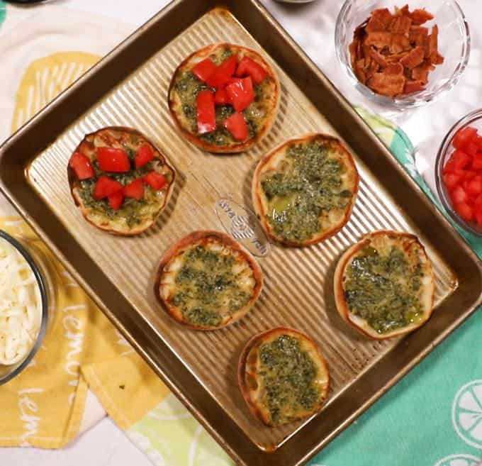 English Muffin halves broiled with pesto and topped with tomato for a pesto pizza.