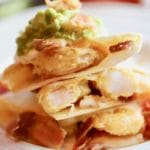 Shrimp and Bacon Quesadillas cooked and ready to eat with avocado and tomato garnish