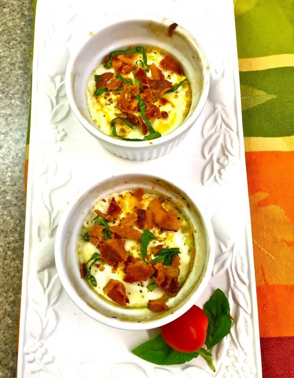 Two Baked Egg Cups garnished with bacon and basil on a white serving platter.