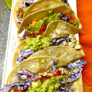 Four salsa verde chicken Tacos on a white serving platter.