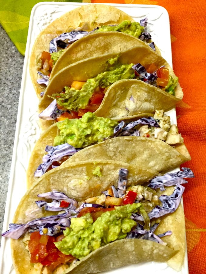 Salsa Verde Chicken Tacos lined up on a rectangular white serving dish