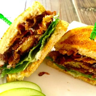 Ultimate BLT sandwich cut in half with green sandwich picks on a white plate.