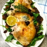 Roast chicken with bread and arugula salad garnished with thyme and cut lemon on a white serving plate.