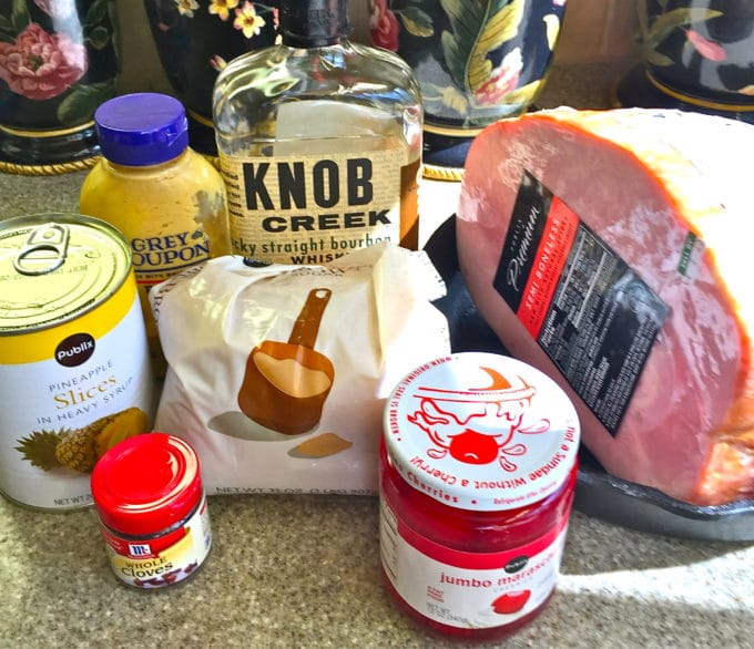 Ingredients for Brown Sugar Bourbon Glazed Ham including pineapple slices, cherries, bourbon and brown sugar