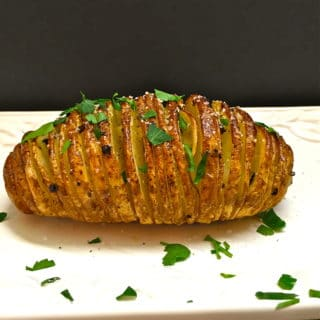 One Hasselback Potato cut in thin slices and garnished with parsley on a cutting board.