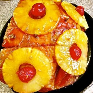 Brown Sugar Bourbon Glazed Ham in a cast iron skillet covered with pineapple slices, cloves and cherries