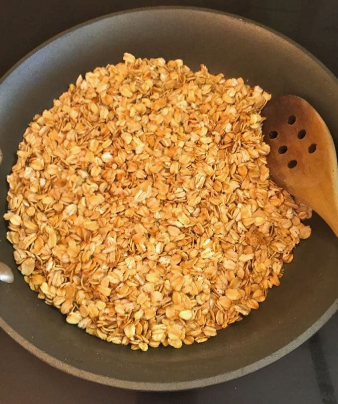 Toasting oatmeal in a skillet for oatmeal muffins.