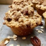 An oatmeal muffin with an oatmeal crumble topping on a baking sheet.