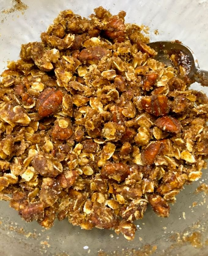 Oatmeal muffin topping of oats, butter, nuts, and brown sugar in a bowl.