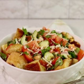 A white serving bowl with a salad with toasted croutons, fresh summer tomatoes and cucumbers.