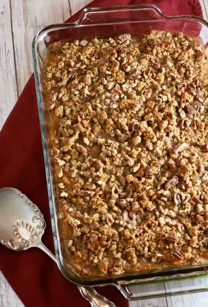 A clear glass baking dish with a sweet potato casserole topped with pecans.