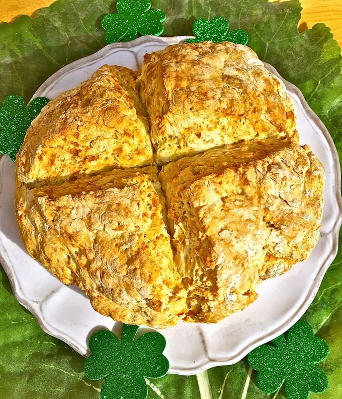 Traditional Irish Soda Bread on a white plate and garnished with shamrocks
