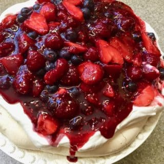 Ultimate Triple Berry Pavlova Dessert on a white cake plate.