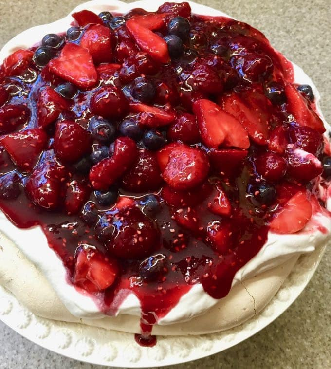Ultimate Triple Berry Pavlova Dessert on a white cake plate.
