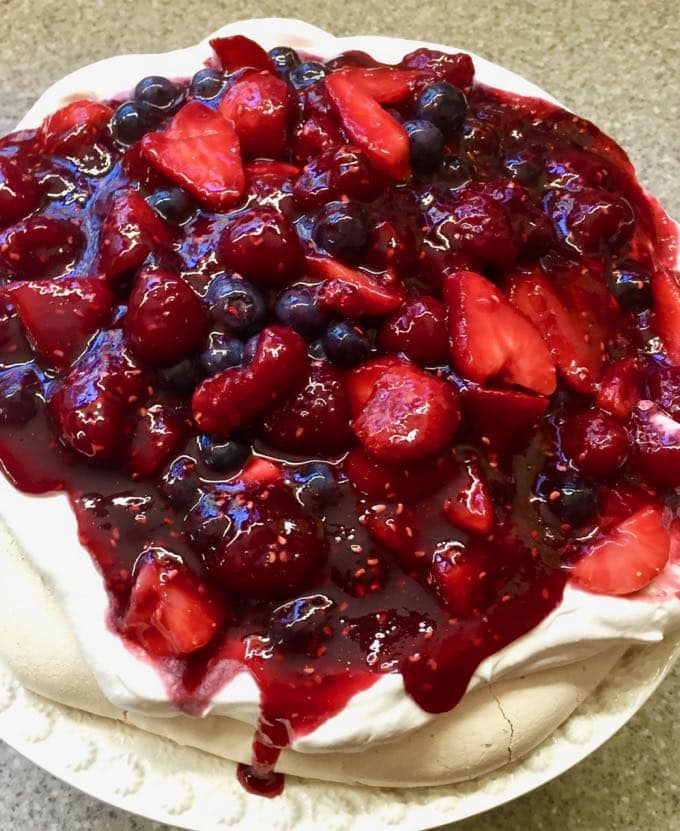 The Ultimate Triple Berry Pavlova Dessert or Meringue Cake on a cake stand.