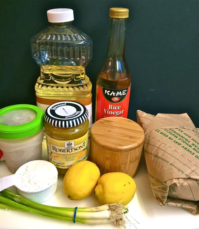 Chicken lemon breast recipe ingredients on a cutting board including chicken breast and lemon curd.