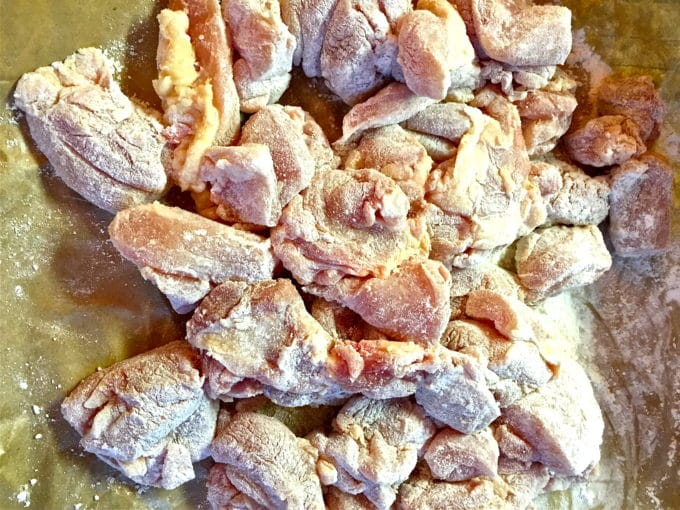 Cut up chicken pieces covered with flour on wax paper.