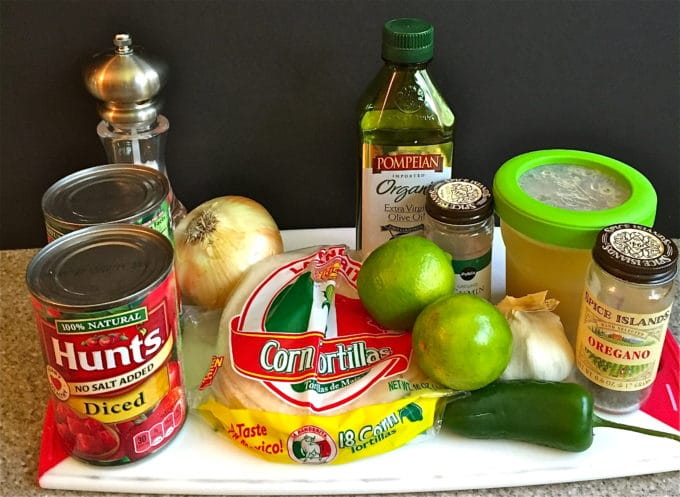 Soup ingredients including canned diced tomatoes, limes, chicken broth, onion and olive oil.