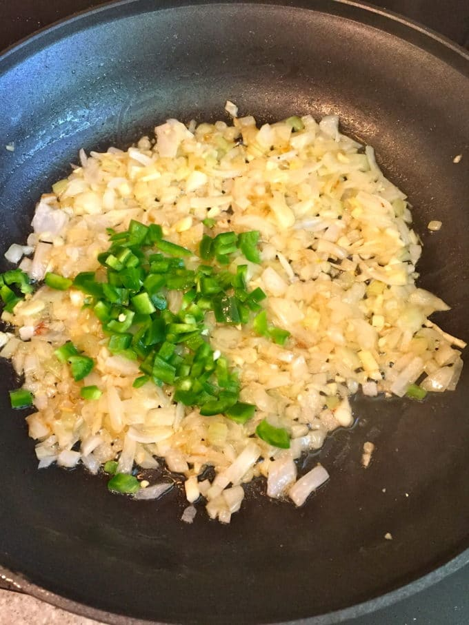 Onions and jalapeños cooking in a skillet.
