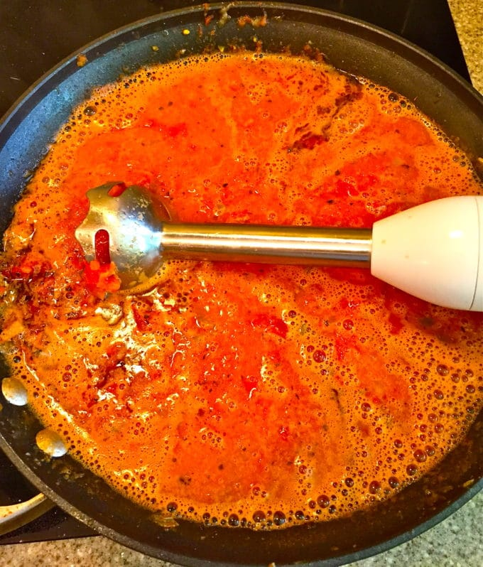 Using an immersion blender to puree soup in a skillet.