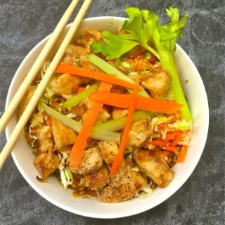 Chicken egg roll bowl garnished with celery and carrots and a pair of chop sticks.
