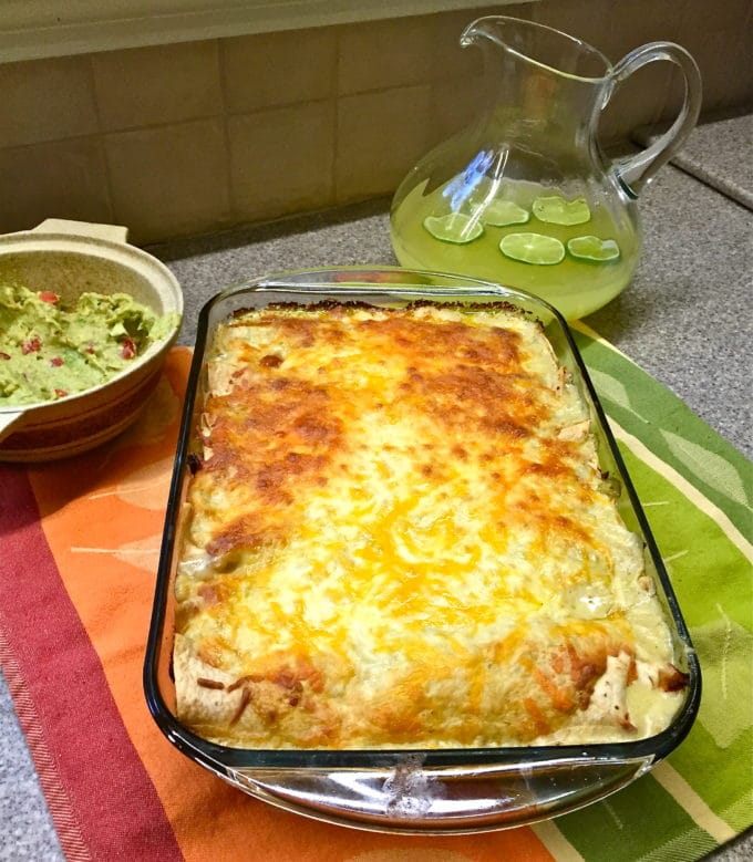 Easy Tequila Lime Chicken Enchiladas in a glass baking dish with a pitcher of margaritas
