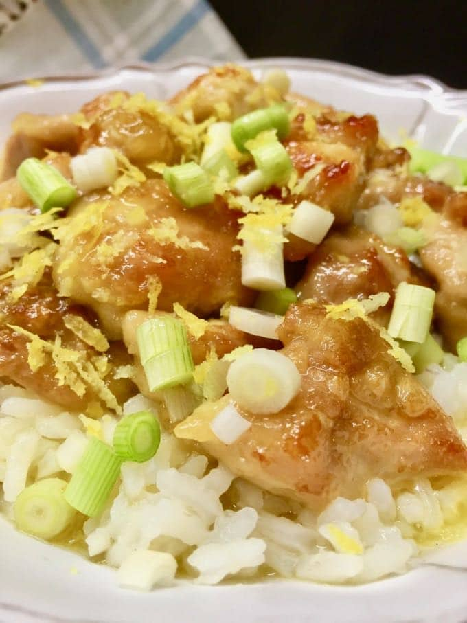 Lemon chicken breast garnished with scallions and lemon zest on a bed of white rice in a white bowl.