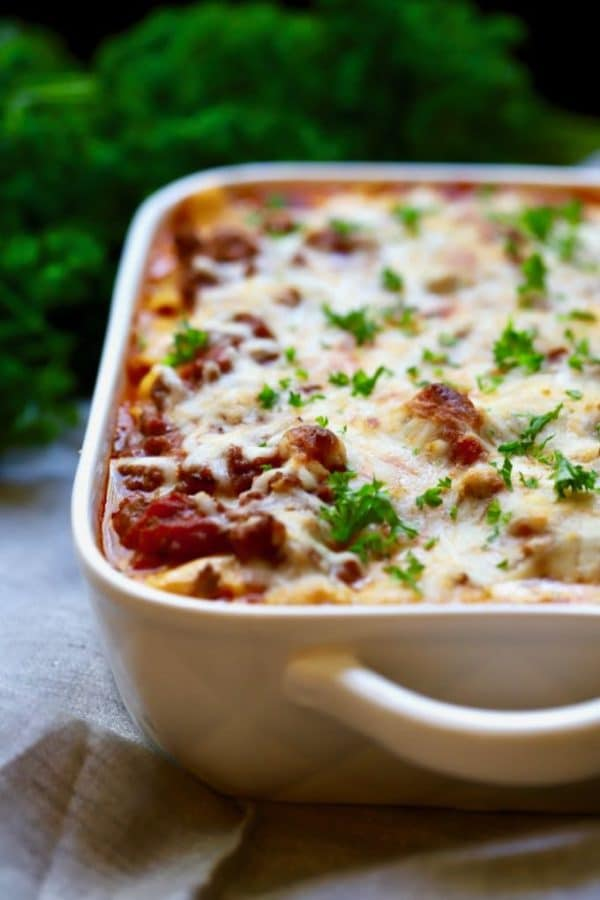 Easy Make Ahead Baked Ziti in a white baking dish garnished with fresh parsley