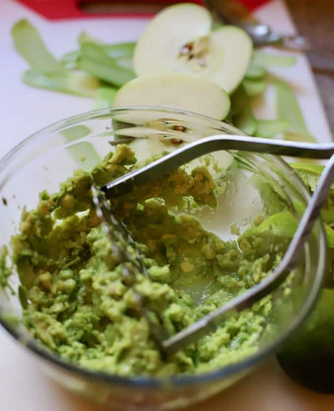 Mashing the avocado for Fish Taco Bowl with Green Apple Guacamole