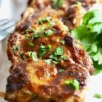 Broiled chili rubbed chicken thighs on a white serving plate garnished with parsley.