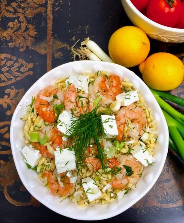 Easy Shrimp Salad with Pasta in a white bowl with lemons, tomatoes and scallions on the table