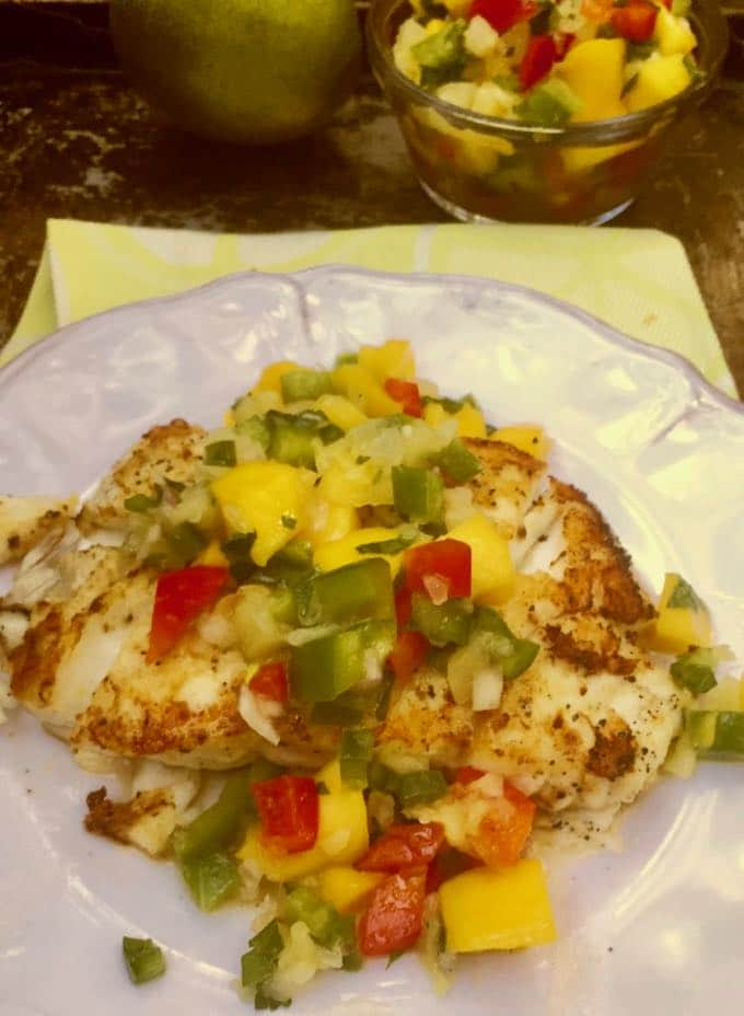A plate of grilled grouper topped with colorful mango salsa and ready to eat