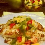Grilled Grouper topped with mango salsa on a white dinner plate