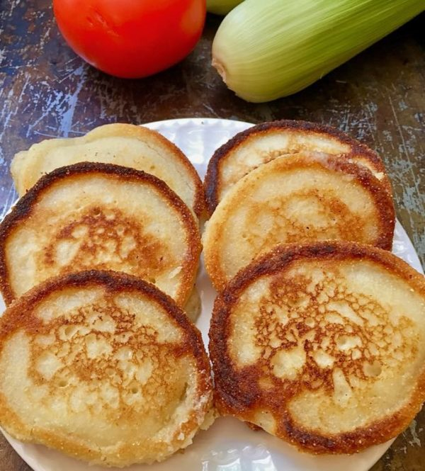 Hoecakes aka Cornmeal Pancakes on a white plate with an ear of corn and tomato in the background