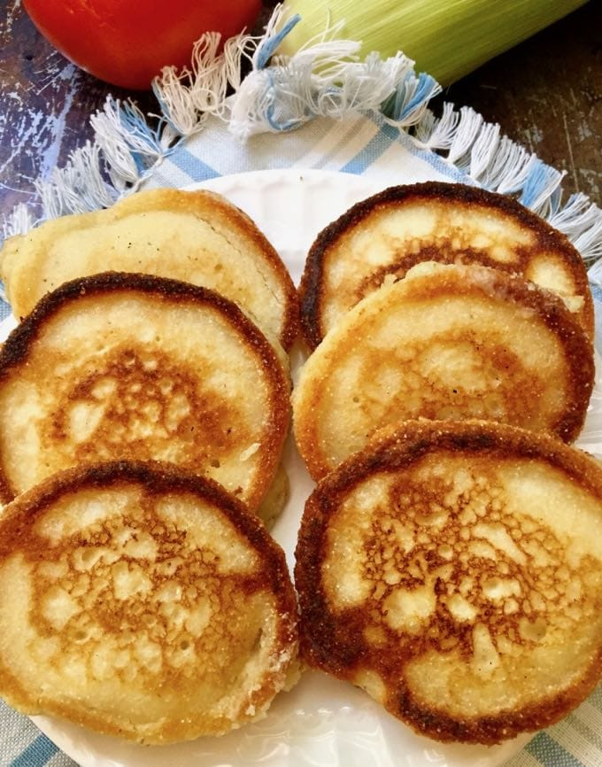 Hoecakes aka Cornmeal Pancakes on a white plate which is on top of a blue and white cloth napkin
