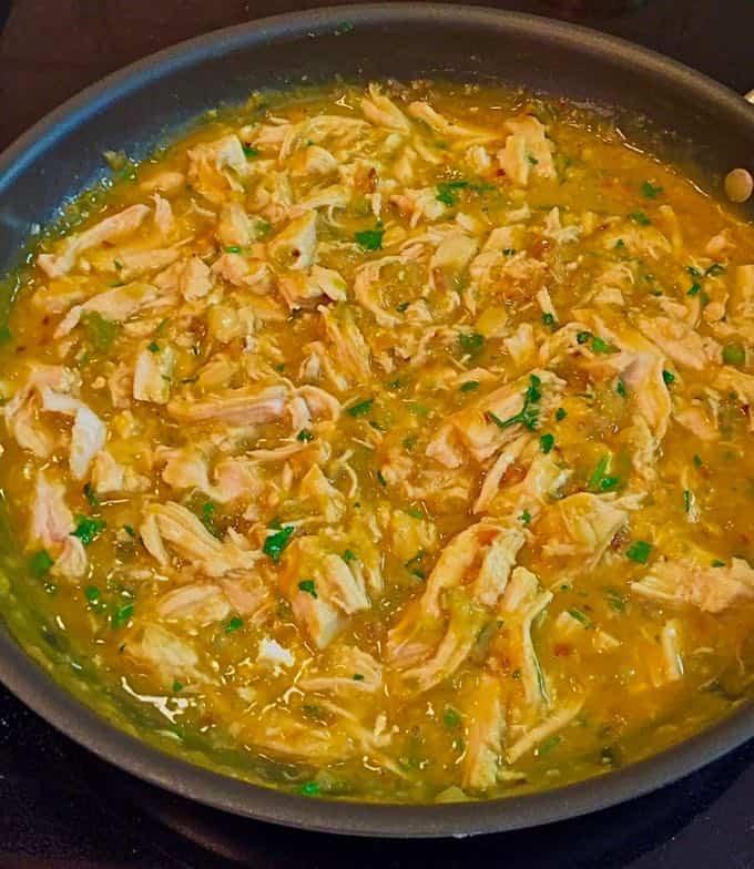 A large skillet full of salsa verde chicken enchilada filling.