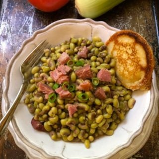Southern Pink Lady Peas in a white bowl topped with chunks of ham and a hoecake