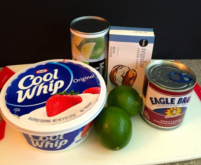 Key lime mousse Ingredients on a cutting board including limes and cool whip.