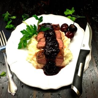 Grilled Pork Tenderloin with Dark Cherry Sauce on a white dinner plate, garnished with parsley, dark cherry sauce, and fresh cherries.