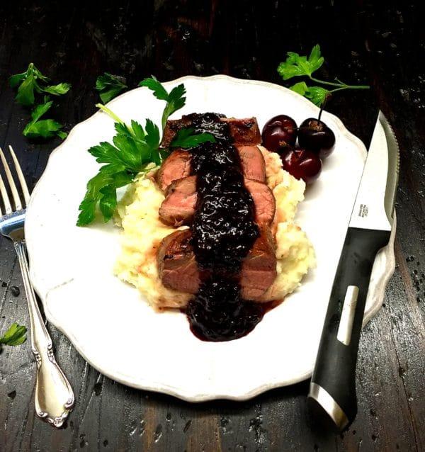 Grilled Pork Tenderloin with Dark Cherry Sauce on a white dinner plate, garnished with parsley, dark cherry sauce, and fresh cherries.