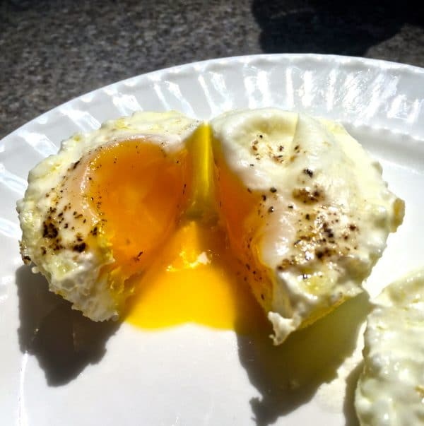 A cooked egg cut in half showing a runny egg on a white plate.
