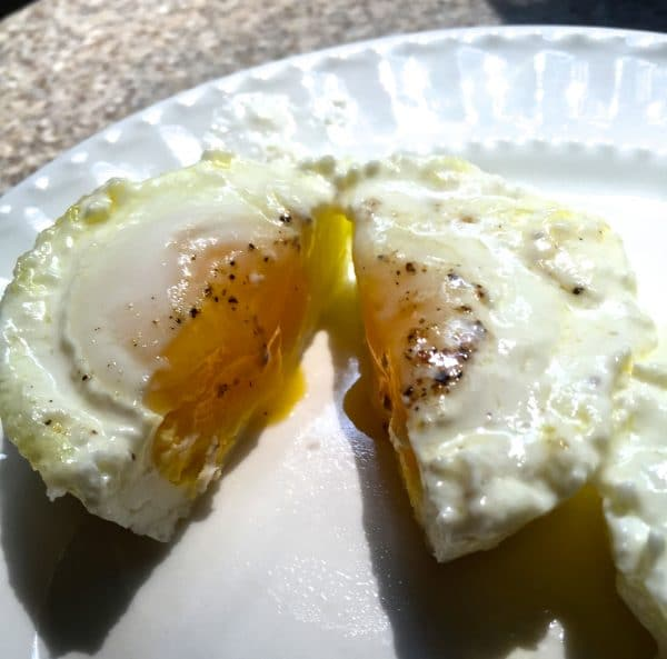 A cooked egg cut in half showing a harder yoke on a white plate.