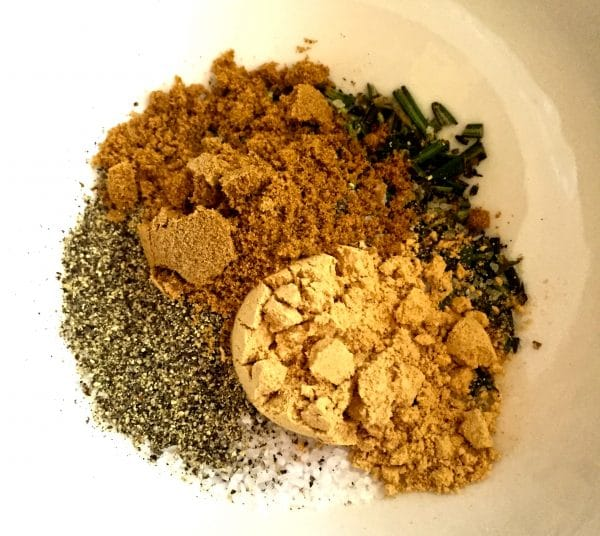 In a small white bowl is rosemary, salt, pepper, cumin, and ginger.