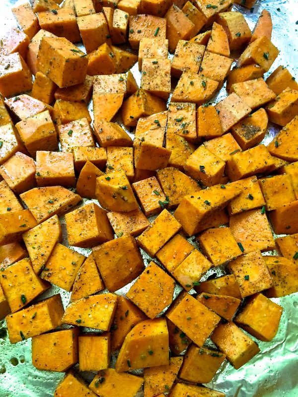 On aluminum foil is sweet potato cubes mixed with the seasoning.