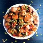 Roasted Sweet Potato Salad topped with toasted pumpkin seeds in a white bowl.