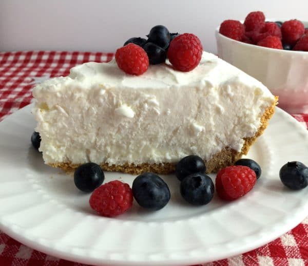 A piece of Frozen Lemonade Pie with blueberries and strawberries.